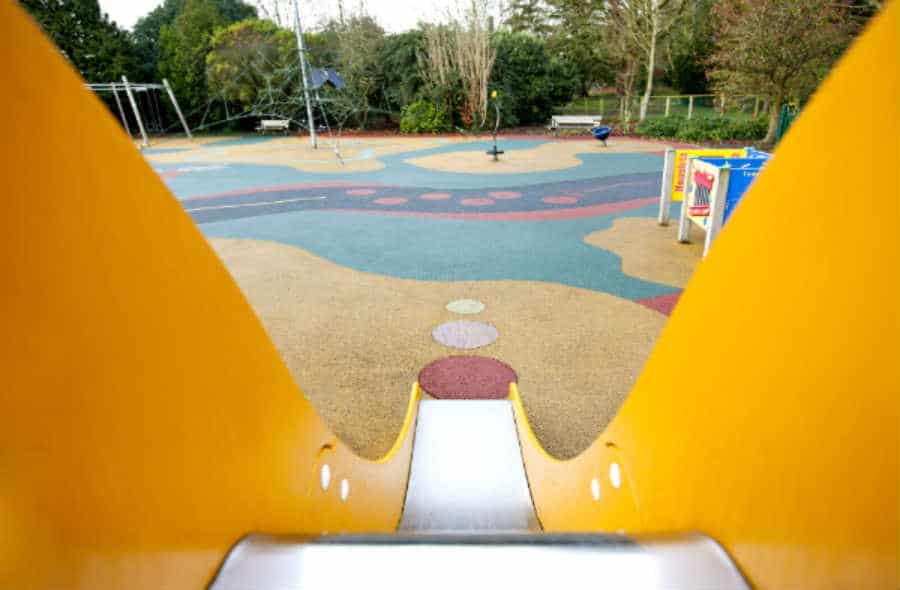 A slide leads to a playfully painted playground surface