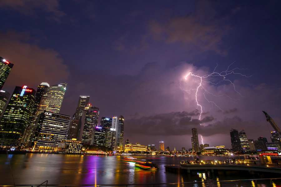 Dramatic shot of lightning striking a building in a city at night
