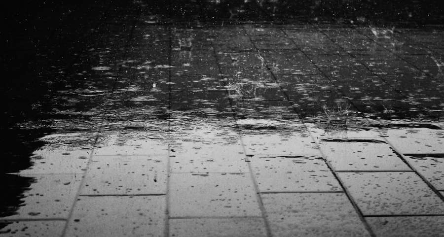 Inclement weather illustrated through rain drops hitting a brick floor