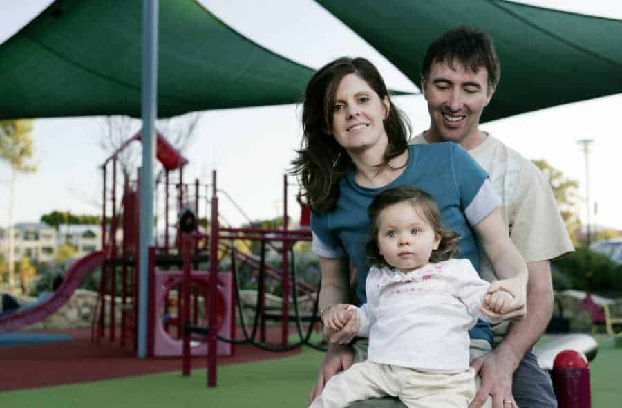 A family at a playground with artificial shade structures