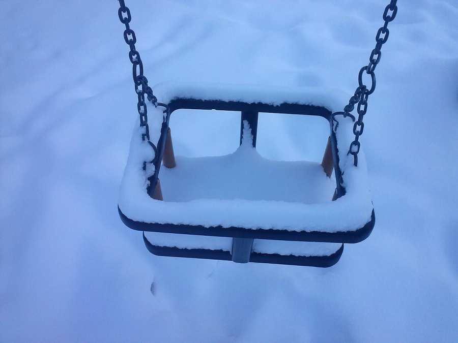 A playground swing covered in snow