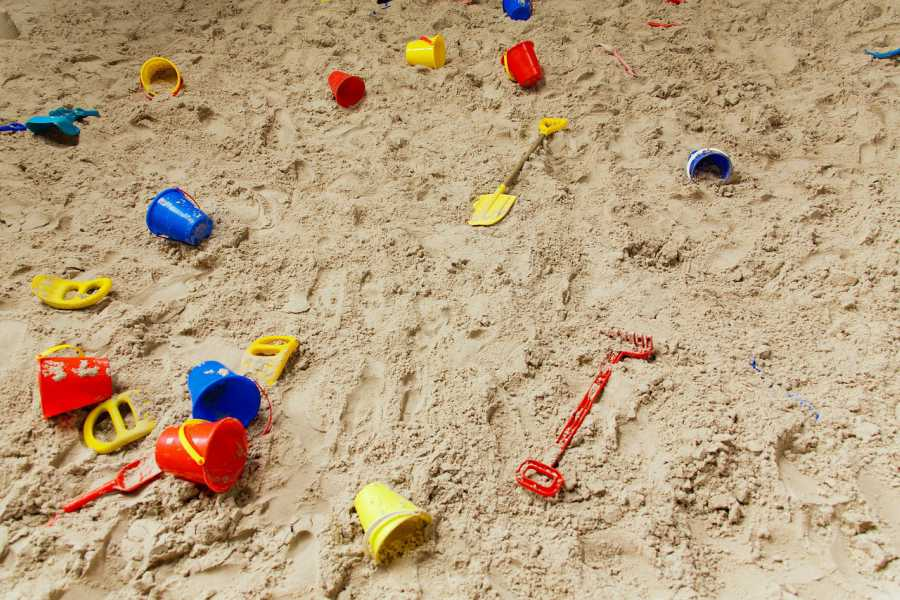 A sandbox filled with toy shovels, buckets, and other tools