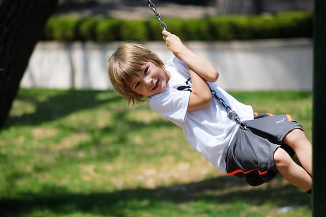 Young child enjoying a playground swing