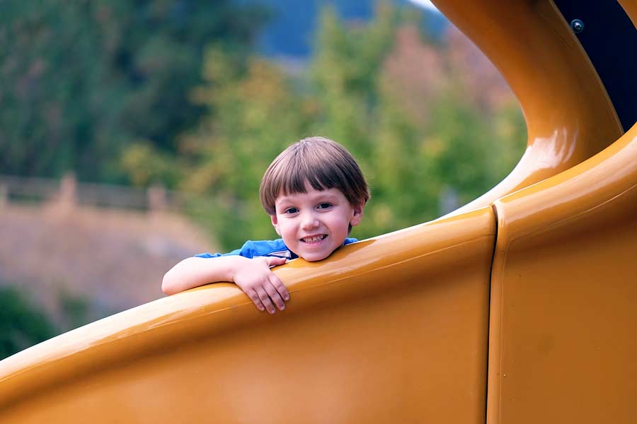 Boy playing on a large spiral slide