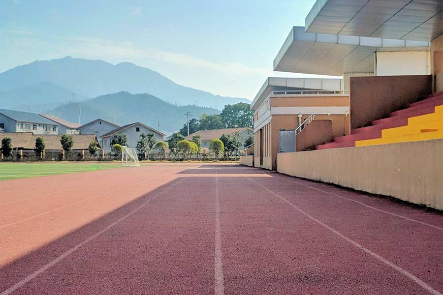 A newly renovated school track with nearby neighborhood homes in the distance