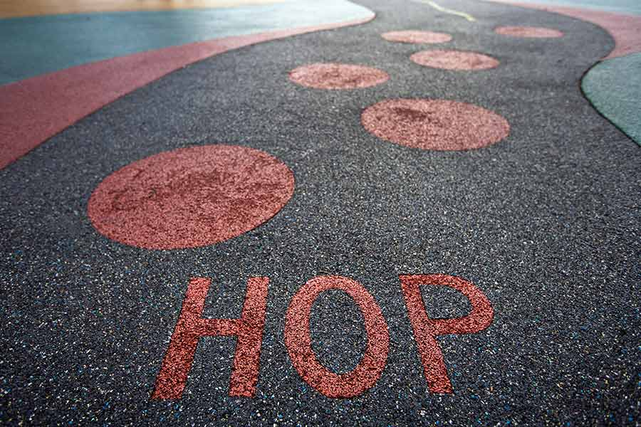 """Colorful pour-in-place rubber surface on a playground with the text """"HOP"""""""