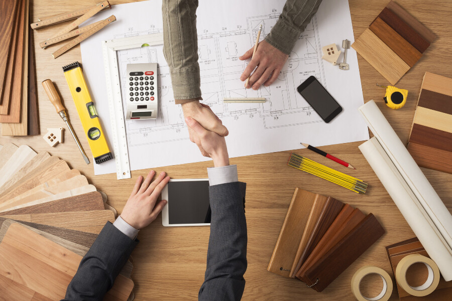 A general contractor shaking hands with a client over a new construction project blueprint.