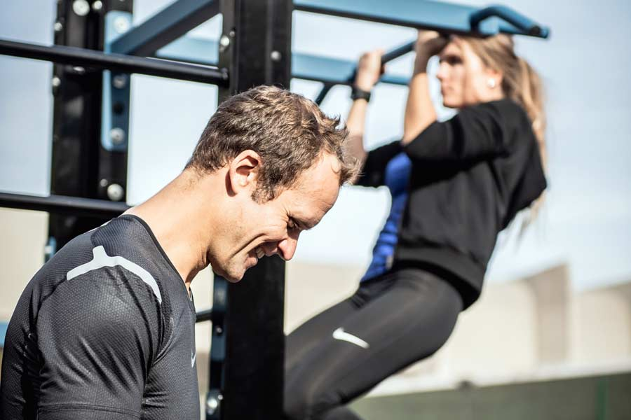 Man and woman using outdoor exercise equipment